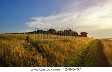 The remains of an old stone sanctuary near the Big Allaki lake in Southern Urals in Chelyabinsk region Russia. Selective focus at the stones. Summer sunset landscape. Soft filter processing.