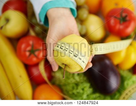 Close up of nutritionist's hand measuring yellow apple with tape over healthy food background. Concept of fat prevention and lose weight.