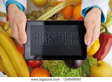 Close-up of doctor's hands holding tablet pc over fresh colorful fruits background. Medicine and technology.