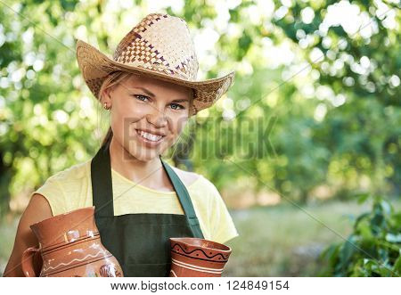 Smiling woman farmer holding old clay pitchers for beverage. Young winemaker with potteries of wine working in vineyard.
