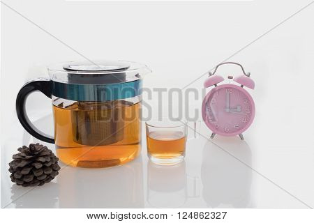 Hot tea set with glass cup and glass pot on isolated background with pink clock on tea time at 3 o'clock  / Hot tea set with glass cup and pot on isolated background at tea time