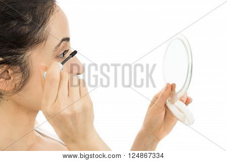 Caucasian woman applying mascara by looking to her mirror. Isolated on white background. ** Note: Shallow depth of field