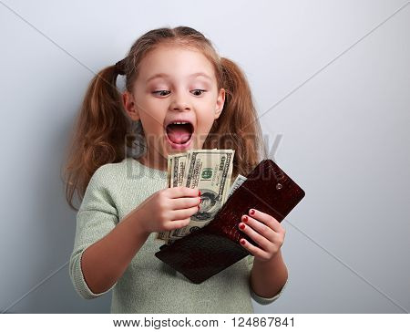 Cute surprising kid girl holding wallet and looking on dollars with open mouth and think how can to spend so much money. Happy childhood.
