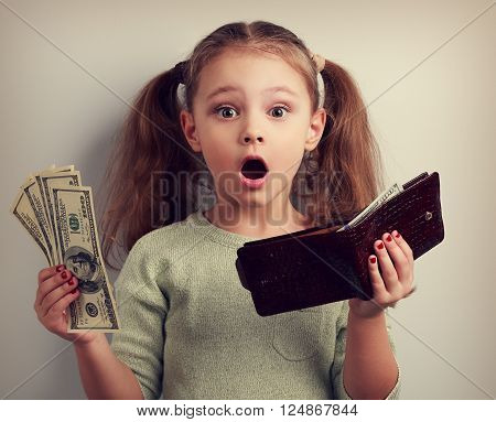 Cute surprising kid girl holding wallet and dollars with open mouth and think how can to spend so much money. Happy childhood. Toned closeup portrait