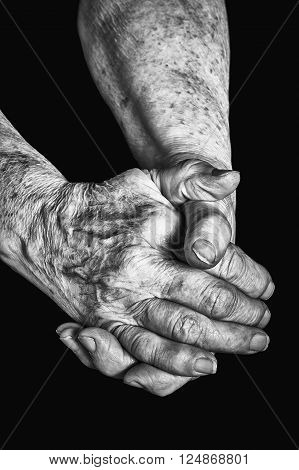 Old woman clasps her hands on a black background