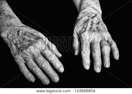 Old hands of woman on a black background