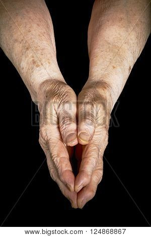 Old woman clasped in her hands on a black background