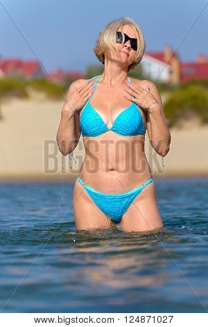 Young woman in blue bikini stands in sea and sprinkles the water