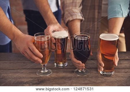 Male group holding glasses of dark and light beer at the table