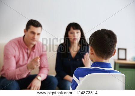 Parents berating their son indoors