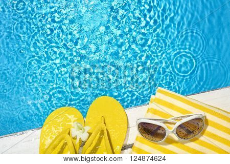 Flip flop,towel and sunglasses on the side of a swimming pool