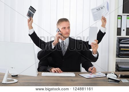 Busy Businessman Multitasking At Desk In Office