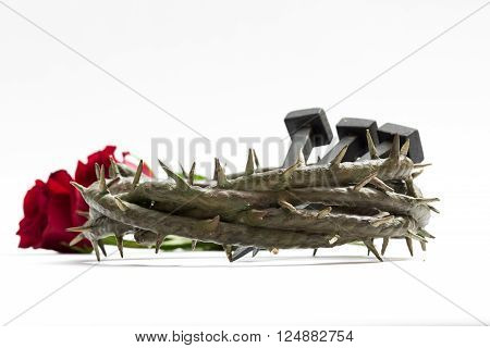 Jesus Christ crown of thorns, nails and two roses on a white background.
