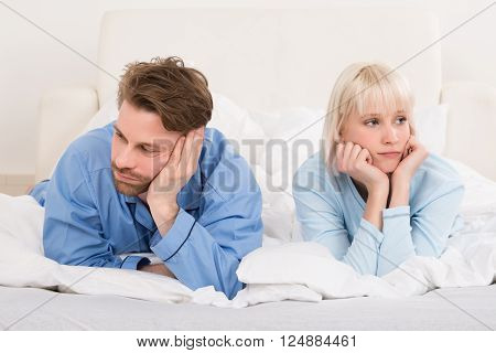 Sad Couple Lying In Bed Ignoring Each Other In Bedroom At Home