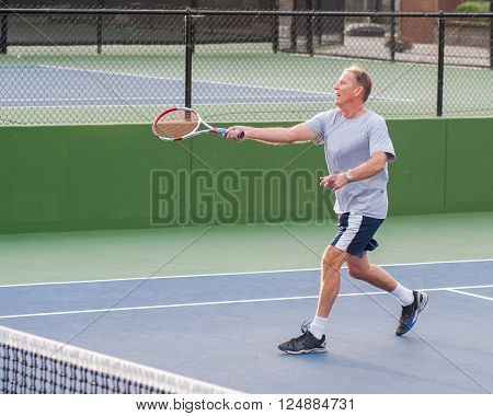 Senior age man showing perfect follow through on volley