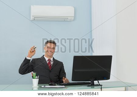 Mature Happy Businessman Sitting On Chair Using Air Conditioner In Office