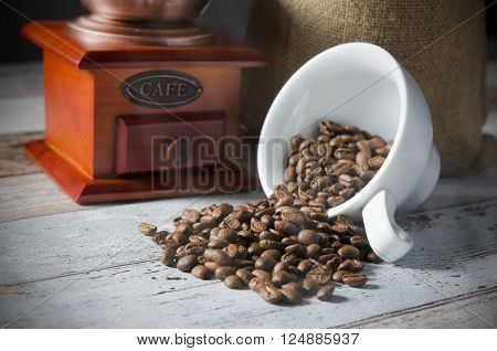 Coffee Grain Spill From A Cup. Jute Bag Of Roasted Beans And Mill