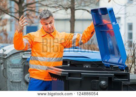 Street Cleaner Looking In Dustbin