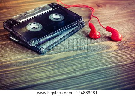 Audio cassette tapes and red earphones over wooden table vintage style selective focus