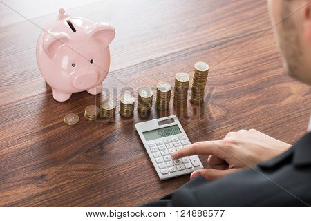 Close-up Of Businessman Using Calculator