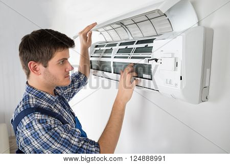 Photo Of Young Male Technician Repairing Air Conditioner poster