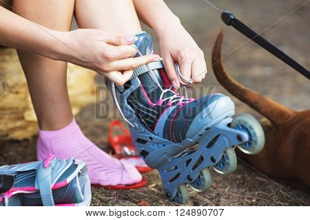Woman is going rollerblading. Sitting on a bench in a park and putting on inline skates. girl with a dog. Close up. Sport lifestyle.