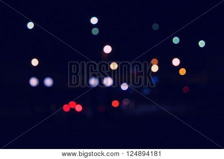 Bokeh and flare of blured urban night scene. Defocused city lights at night time. Toned image. Vintage color.