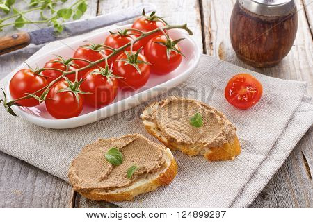 Homemade chicken liver pate on  baquette and tomatoes on textile napkin