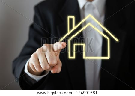 Businessman choosing house, real estate concept. Hand pressing the house icon. Copy space.