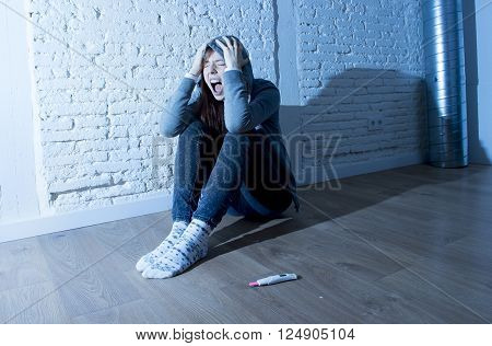 young red hair teenager girl or young woman screaming in shock and overwhelmed after positive pregnancy test sitting on floor devastated and depressed unwanted maternity concept