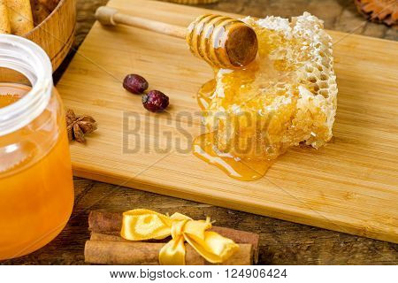 rich floral honey and honeycombs on a wooden support close up