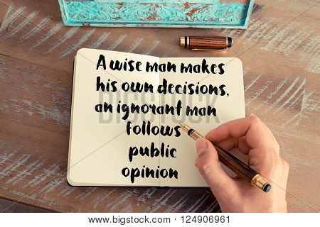Retro effect and toned image of a woman hand writing on a notebook. Handwritten quote A wise man makes his own decisions, an ignorant man follows public opinion as inspirational concept image