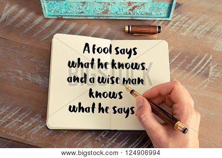 Retro effect and toned image of a woman hand writing on a notebook. Handwritten quote A fool says what he knows, and a wise man knows what he says as inspirational concept image
