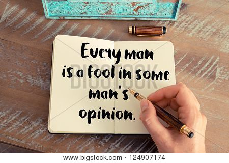 Retro effect and toned image of a woman hand writing on a notebook. Handwritten quote Every man is a fool in some man's opinion as inspirational concept image