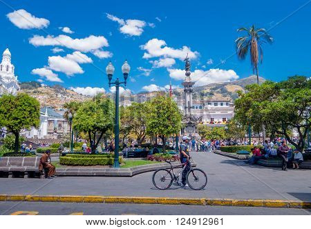 QUITO, ECUADOR - MARZO 23, 2015: Unidentified man and his bycicle passing trought the independence square in Quito, day to make some sports, people walking around