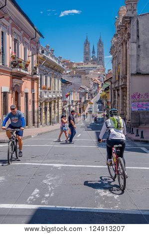 QUITO, ECUADOR - MARZO 23, 2015: A little hill appears in the route of this unidentified cycler, sunny day to do sports. Basilica church at the top