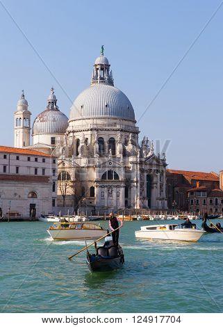 Venice, Italy - March 22, 2016: Gondoliers and Gondola at Venice grand canal with the Basilica di Santa Maria della Salute in the background