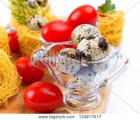 Glass Gravy boat with quail eggs. On the background of pasta nests and cherry tomatoes.