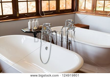 sanitary, plumbing and washing concept - close up of bathroom with two bathtubs