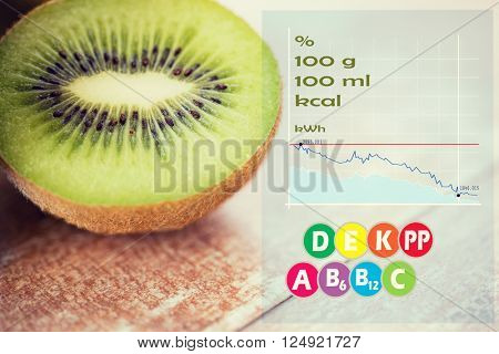 fruits, diet, food and objects concept - close up of ripe kiwi slice on table with calories and vitamin chart poster