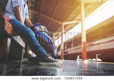 Portrait of a young man traveler waiting for train and travel bag.