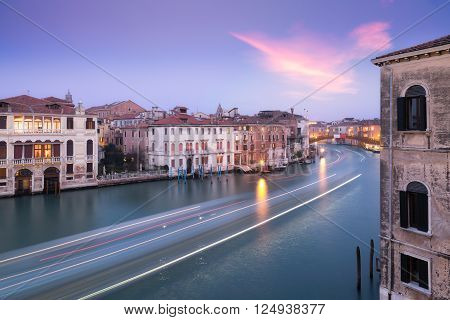 Boat trails passing along the Grand Canal in Venice at dusk with lights on in the surrounding buildings looking towards the Accademia Bridge