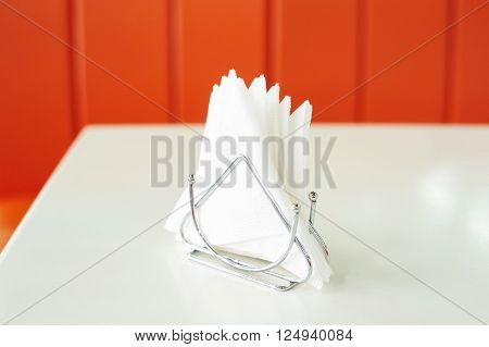 Napkin holder with white napkins on red background. Pile of napkins