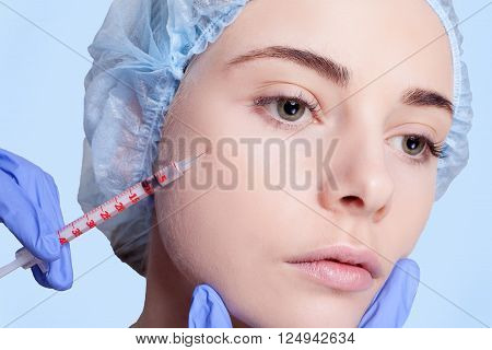 Attractive young woman gets cosmetic injection an injection in the upper lip over white background. Doctors hands making an injection in face close-up. Beauty Treatment.