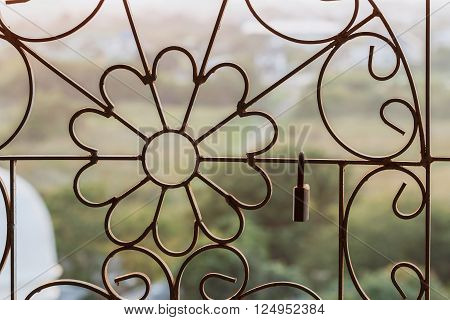 Master key on old iron background hanging on the wrought iron bars