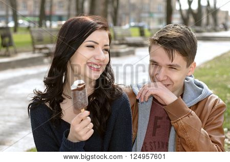 Portrait of a couple on vacation. Girl eating ice cream and they laugh gaily. Concept: love, relationship, friendship.