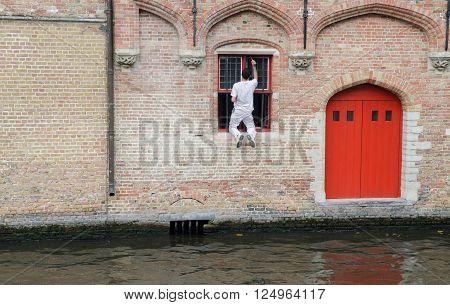 Unsafe work - unsafe window painting in Brugge. Belgium