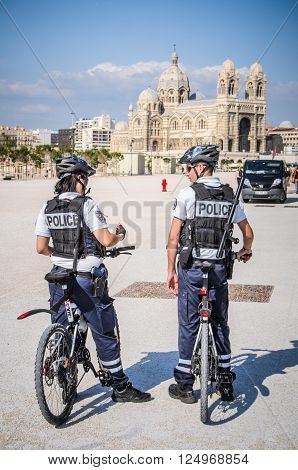 MARSEILLES FRANCE - MAY 7 2014: Two French police officers on bikes in front of Marseilles Cathedral