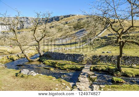 Low bridge over Malham Beck near Malham Cove in attractive landscape with footpath and gate in the stone wall.