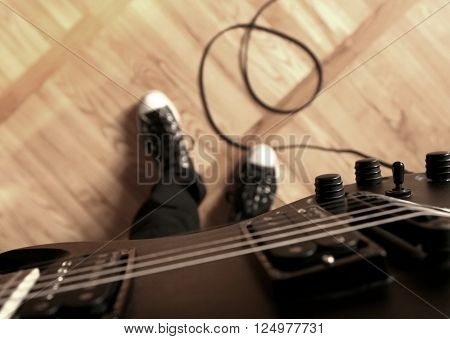 Playing electric guitar. First person perspective: guitar, sneakers, cord.